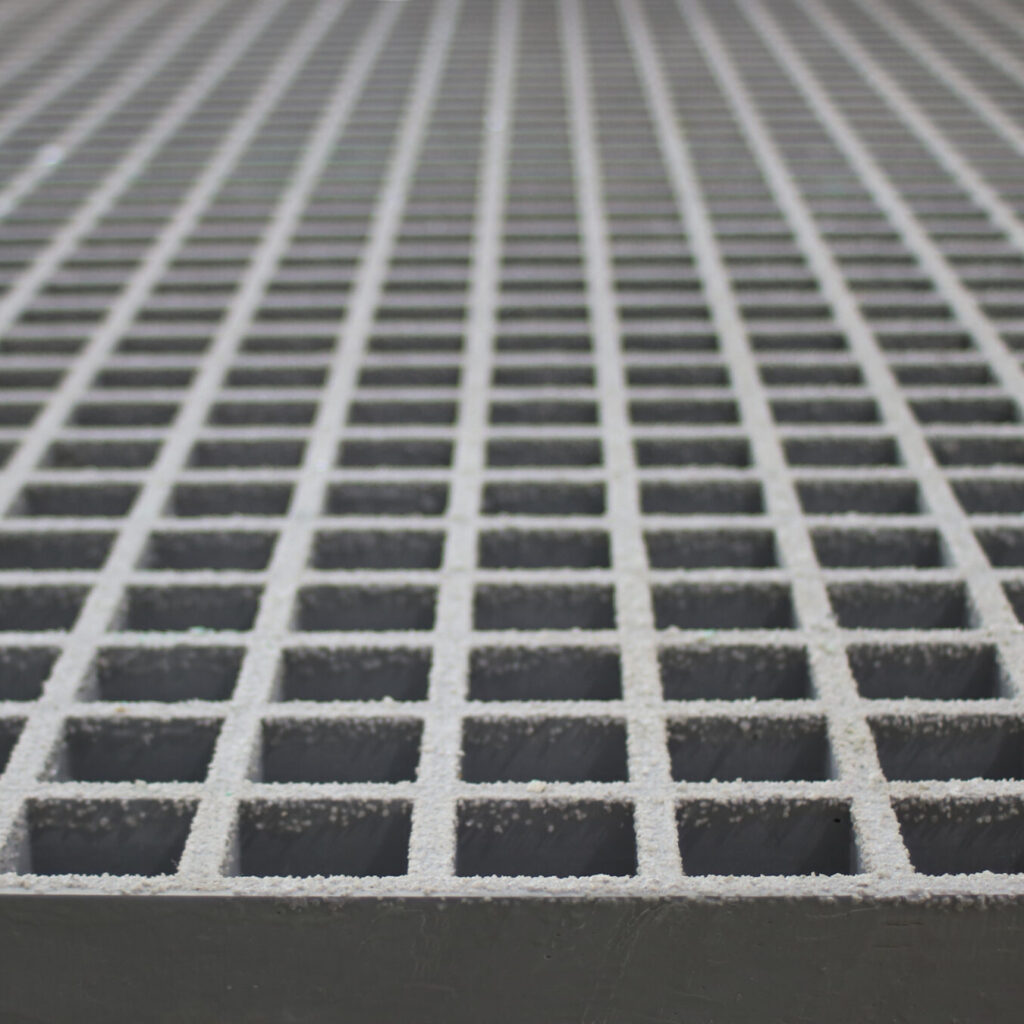 A close-up of a panel of QuartzGrip GRP Open Mesh Grating in grey showing the slip-resistant, gritted finish