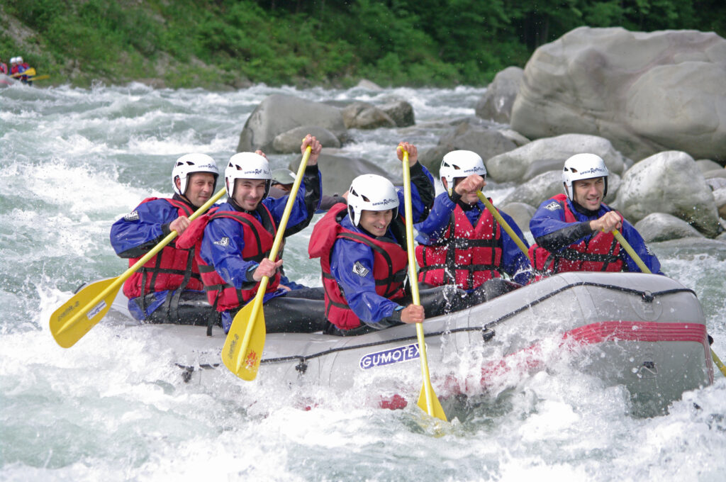 A team of people working together to steer a raft through white water rapids